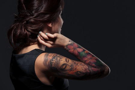 Photo pour Back view of pretty young woman with tattooed hand - image libre de droit