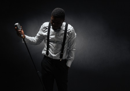 Photo for Portrait of afro american male singer posing over dark background - Royalty Free Image