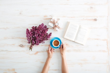 Photo for Hands of young woman drinking coffee and reading book on wooden table with flowers and present box - Royalty Free Image