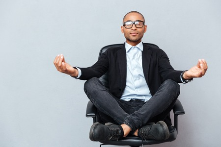 Foto de Closeup of attractive young man in glasses meditating on office chair - Imagen libre de derechos