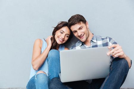 Foto de Portrait of happy young couple using laptop isolated on gray background - Imagen libre de derechos
