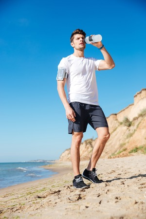 Photo pour Handsome young sportsman standing and drinking water on the beach - image libre de droit