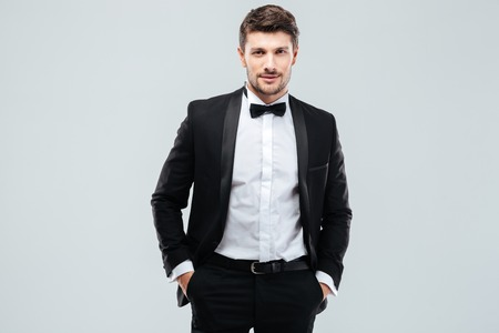 Photo pour Confident young man in tuxedo with bowtie standing with hands in pockets - image libre de droit