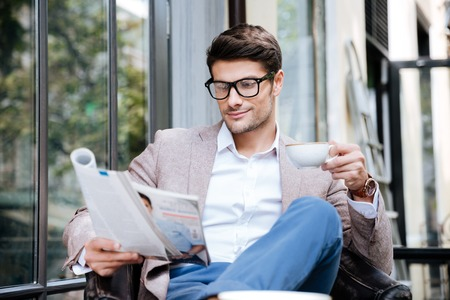 Photo pour Handsome young man in glasses with magazine drinking coffee in outdoor cafe - image libre de droit