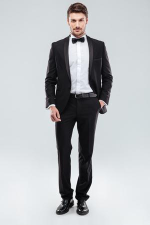 Foto de Confident attractive young man in tuxedo standing with hand in pocket - Imagen libre de derechos