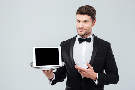 Photo pour Confident young butler in tuxedo holding and pointing at blank screen tablet on tray - image libre de droit