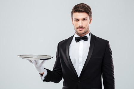 Photo pour Portrait of young butler in tuxedo holding empty tray - image libre de droit