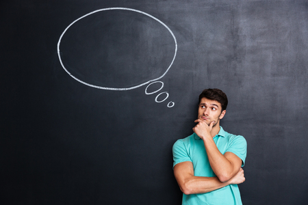 Photo pour Pensive attractive young man with thinking bubble on blackboard background - image libre de droit