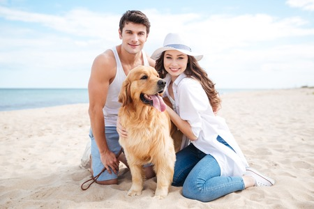 Beautiful young couple with their dog on the beach in summer