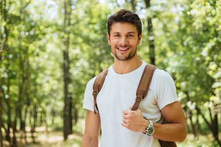 Foto de Closeup of cheerful young man in white t-shirt with backpack standing and smiling in forest - Imagen libre de derechos