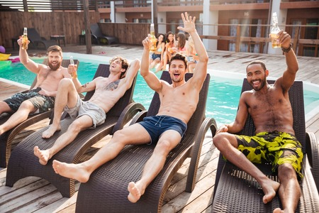 Photo for Handsome young smiling men having fun in swimming pool and drinking beer - Royalty Free Image