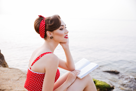 Photo pour Young beautiful pensive pin up girl sitting with book on the rock at the beach - image libre de droit