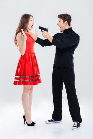 Foto de Full length of criminal man choking and threatening with gun to woman - Imagen libre de derechos