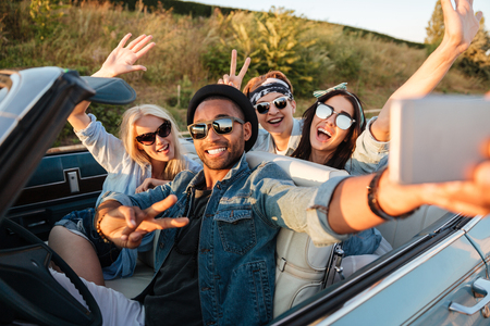 Photo pour Multiethnic group of happy young people taking selfie with smartphone and showing peace sign in the car - image libre de droit