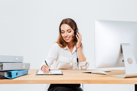 Foto de Smiling young woman making notes while talking with custumer on the phone at the call center over white background - Imagen libre de derechos