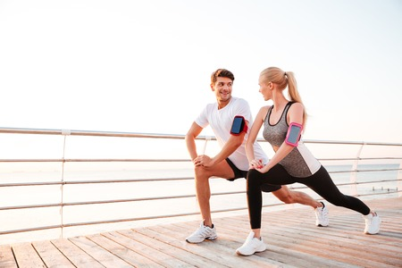 Foto de Athletic young couple doing stretching legs exercises together on the pier - Imagen libre de derechos