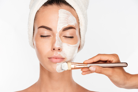Photo pour Portrait of a attractive young woman getting beauty skin mask treatment on her face with brush - image libre de droit