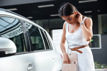 Foto de Pretty young woman standing and looking keys of car in her bag outdoors - Imagen libre de derechos