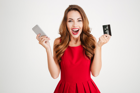 Foto de Cheerful excited young woman with mobile phone and credit card over white background - Imagen libre de derechos