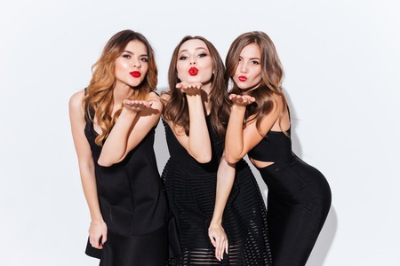 Photo pour Three playful attractive young women standing and sending kisses over white background - image libre de droit