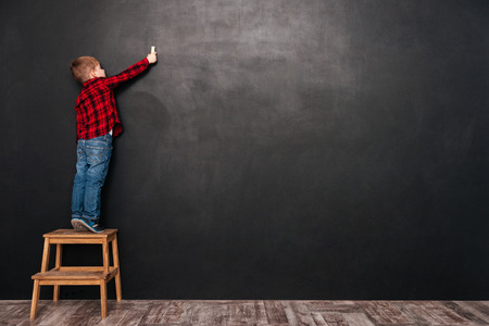 Photo pour Photo of a little cute child standing on stool near blackboard and drawing on it. - image libre de droit