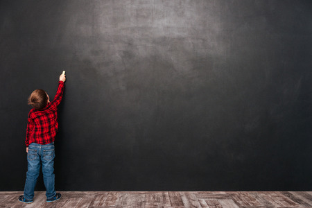 Photo pour Image of a little pretty child standing near blackboard and drawing on it. - image libre de droit