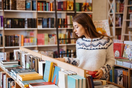 Foto de Portrait of a young casual woman searching for a book in bookstore and looking at camera - Imagen libre de derechos