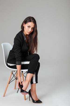 Foto de Pretty fashion model on chair looking at camera. gray background - Imagen libre de derechos