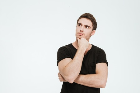 Photo for Picture of young thoughtful man dressed in black t-shirt standing over white background looking aside. - Royalty Free Image