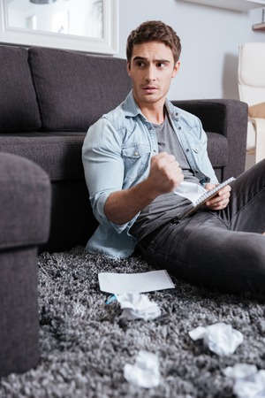 Portrait of a confused casual man holding crumpled sheet of paper with notepad while sitting on carpet at home