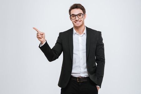 Photo for Portrait of a happy businessman in eyeglasses pointing finger away over white background - Royalty Free Image