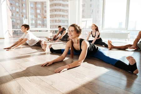 Photo for Group of smiling young people stretching and doing twine on the floor in yoga studio - Royalty Free Image
