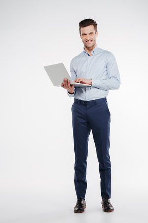 Photo pour Vertical image of Smiling business man which standing in studio with laptop in hand and looking at camera. Isolated white background - image libre de droit
