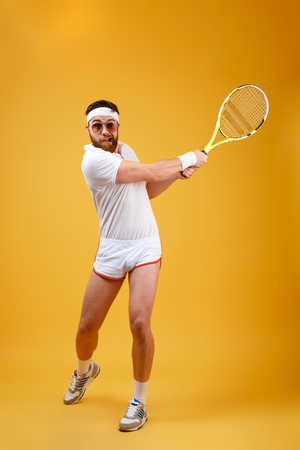Photo for Vertical image of sportsman in sunglasses which playing in tennis. Full length portrait over orange background - Royalty Free Image