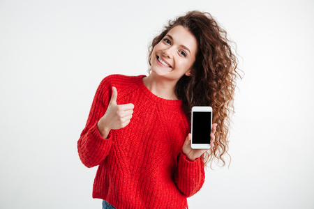Photo pour Smiling young woman showing blank smartphone screen and thumbs up over white background - image libre de droit