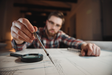 Concentrated bearded man holding compass over the graph on a desk, focus on a compass
