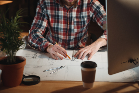 Close up portrait of man in plaid shirt working with graph and computer at the office
