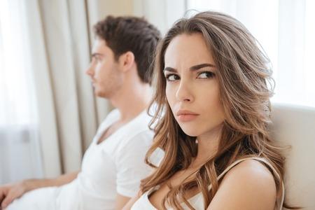 Photo pour Sad unhappy young couple having problems in bed - image libre de droit