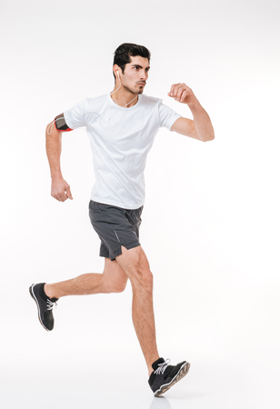 Photo pour Side view full length portrait of a concentrated young sports man running with earphones isolated on a white background - image libre de droit