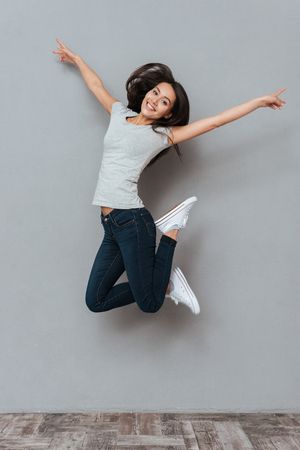 Photo for Vertical image of pretty happy woman jumping in studio and looking at camera over gray background - Royalty Free Image