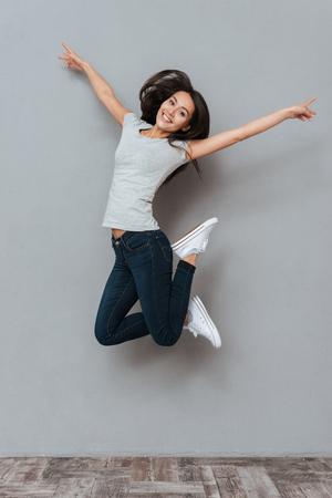 Foto de Vertical image of pretty happy woman jumping in studio and looking at camera over gray background - Imagen libre de derechos