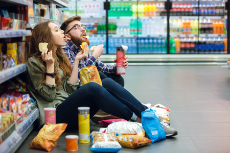 Photo pour Portrait of a young funny hungry couple sitting on the supermarket floor and eating junk food - image libre de droit