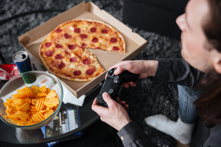 Foto de Cropped photo of young man gamer sitting at home indoors and play games with joystick near pizza and crisps. - Imagen libre de derechos
