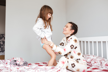 Photo for Careful mother wearing her smiling daughter while sitting in bed - Royalty Free Image