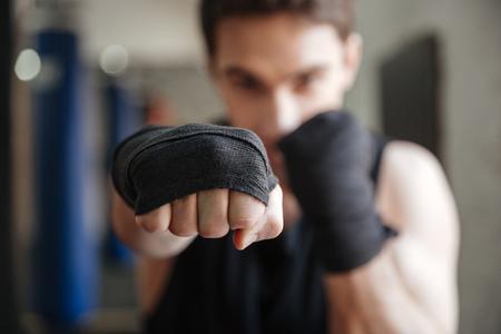 Foto de Close up  view of a young boxer doing exercise in gym. Focus on hand - Imagen libre de derechos