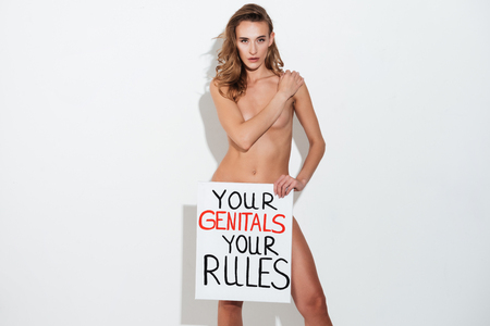 Photo pour Angry woman feminist with poster 'Your genitals your rules' looking camera and hiding breast - image libre de droit