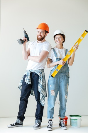 Photo for Full length portrait of a smiling happy couple wearing hardhats and holding tools over white - Royalty Free Image