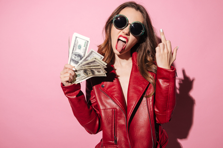 Photo pour Portrait of an arrogant provocative girl in leather jacket holding money banknotes and showing middle finger gesture isolated over pink - image libre de droit