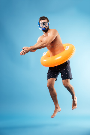 Photo for Man wearing swimming glasses with swimming circle diving isolated over blue - Royalty Free Image