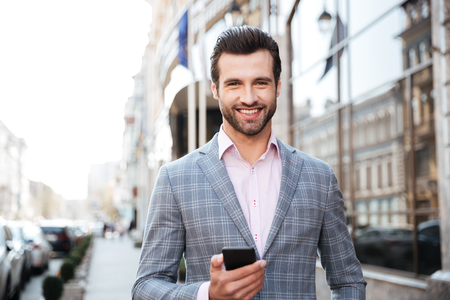 Photo for Portrait of a smiling young man in jacket holding mobile phone in a city area - Royalty Free Image